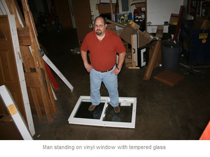 Man standing on vinyl window with tempered glass.